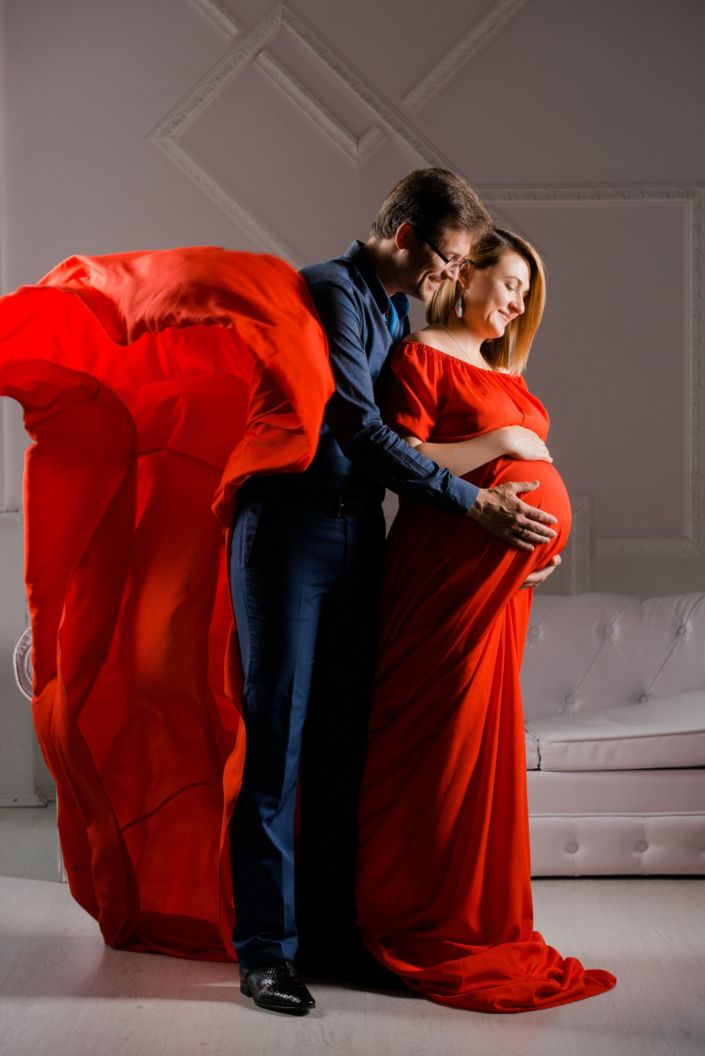 Фотосессия беременных в студии, девушка с мужем на фоне белой стены и дивана