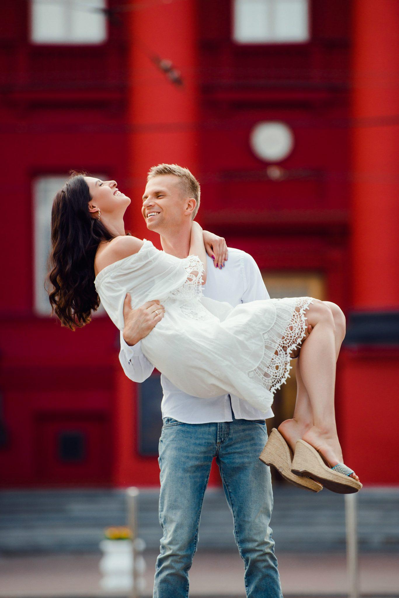 Love Story на природе, на фоне красного корпуса ун. Шевченко, девушка на руках у мужчины