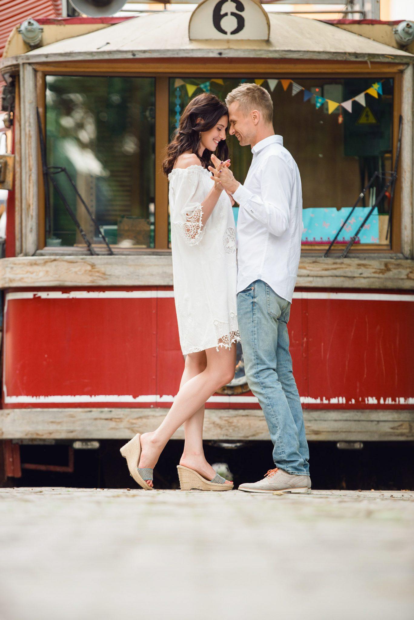 Love Story на природе, пара на фоне старого трамвая красного цвета