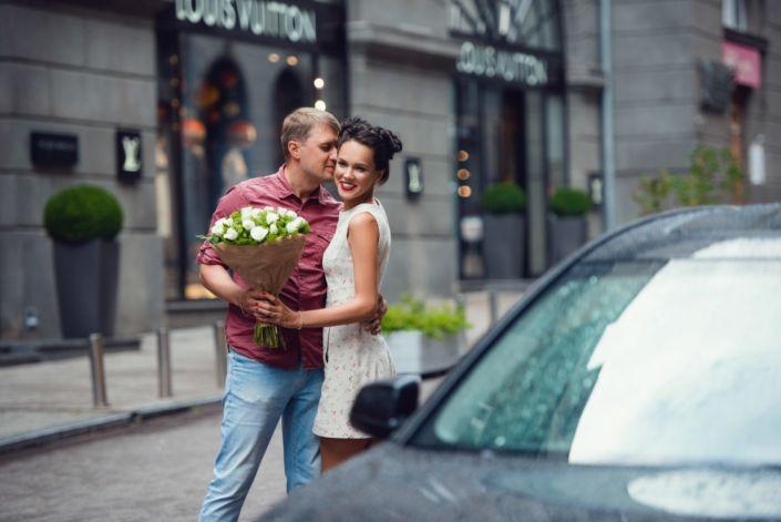 Love story фотосессия, на природе, прогулка по Киеву, пара целуется, у девушки в руках букет белых цветов