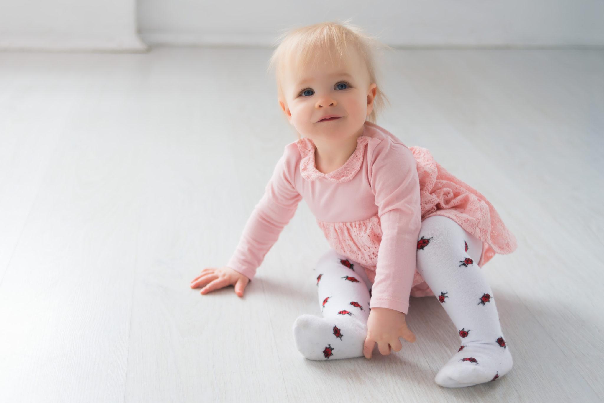 Детская фотосессия, ребенок смотрит на фотографа сидя на полу