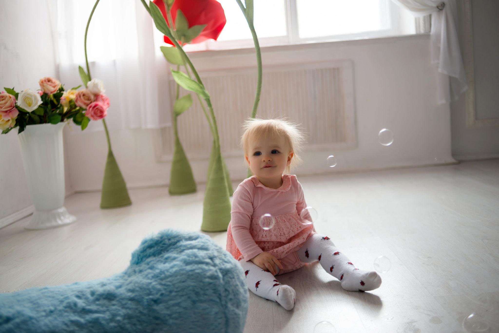 Детская фотосессия, ребенок сидит на полу на фоне цветов