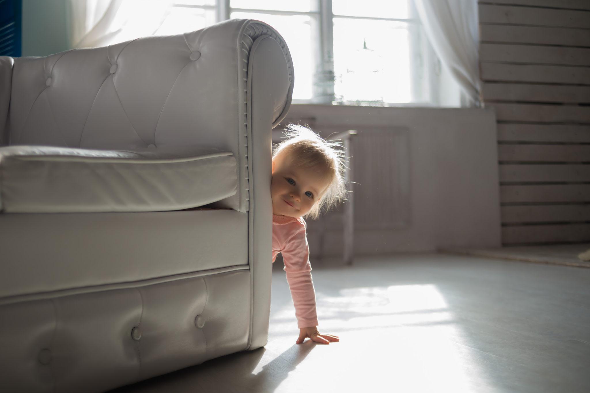 Детская фотосессия, ребенок выглядывает из-за белого дивана