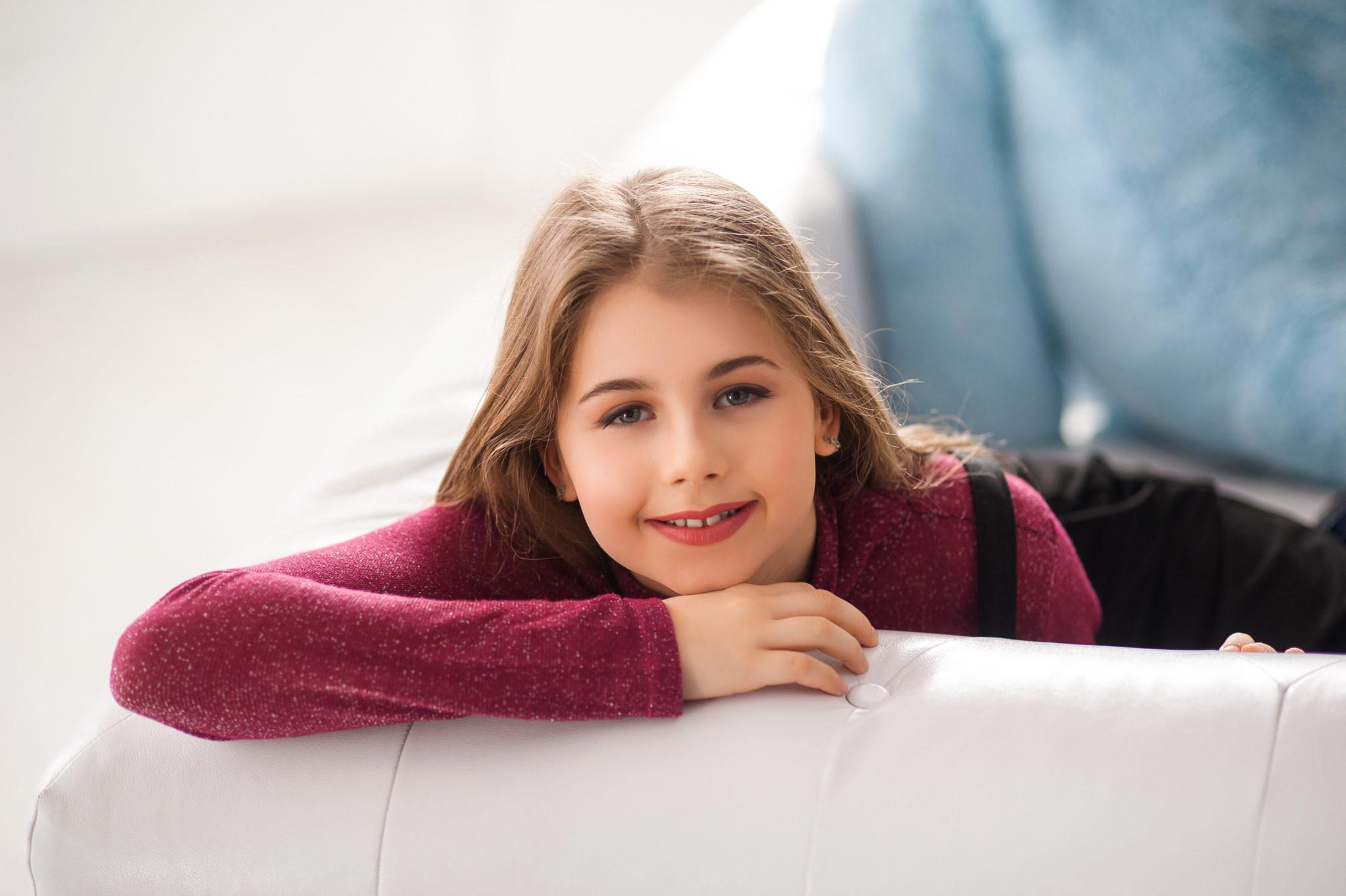 Детская фотосессия, девочка улыбается в камеру сидя на белом диване