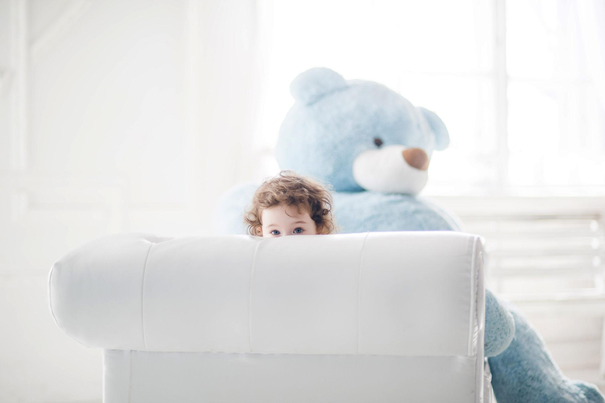 Детская фотосессия, ребенок на диване с большим синим мишкой