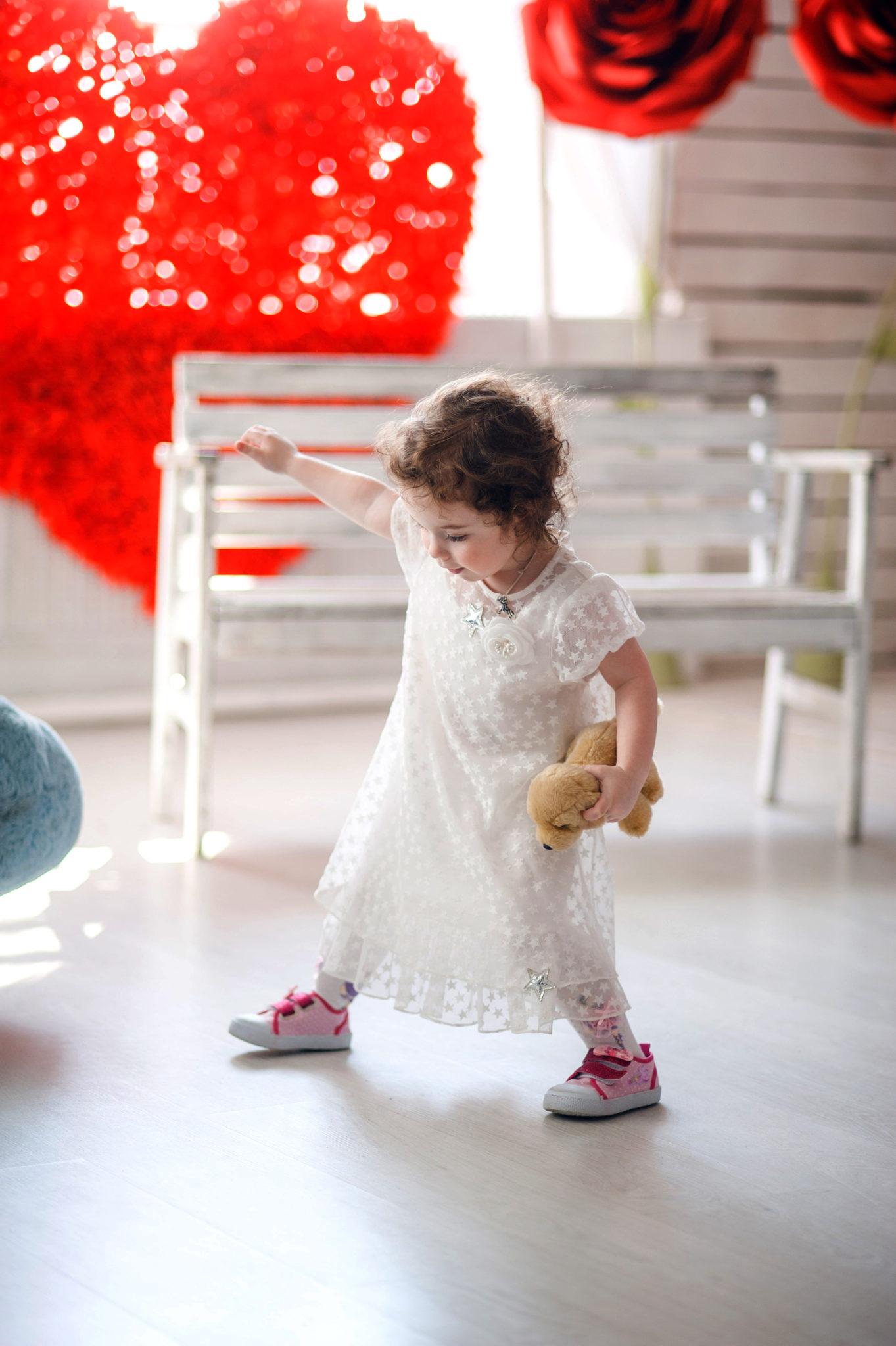 Детская фотосессия, девочка с мишкой в руках на фоне сердца и белой лавочки