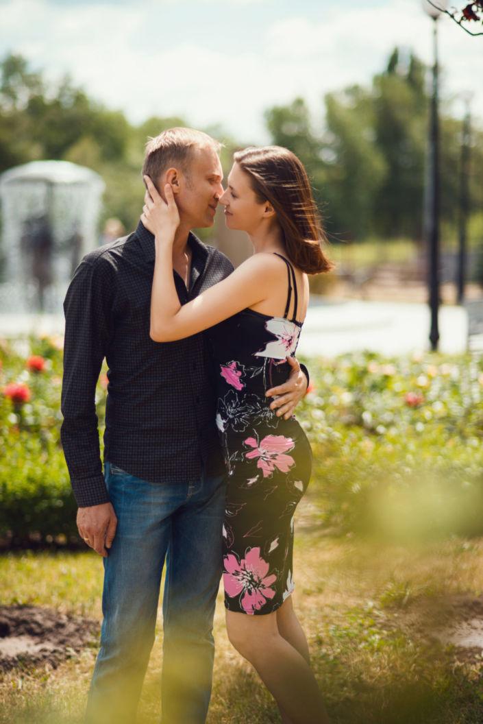 Семейная фотосессия, на природе, пара стоит обнявшись на фоне цветов