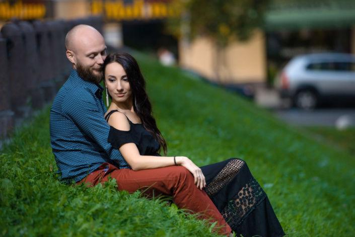 Семейная фотосессия на природе, пара сидит обнявшись на холме заросшем травой