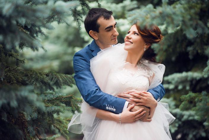 Семейная фотосессия на природе, невеста и жених обнимаются в елях