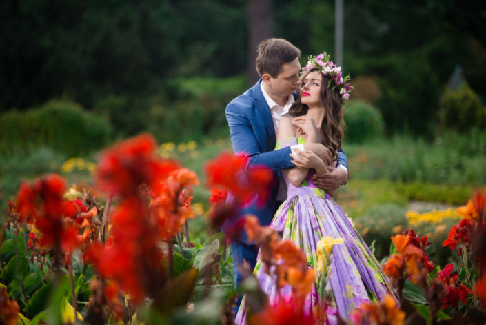 Семейная фотосессия на природе, пара стоит обнявшись в цветах