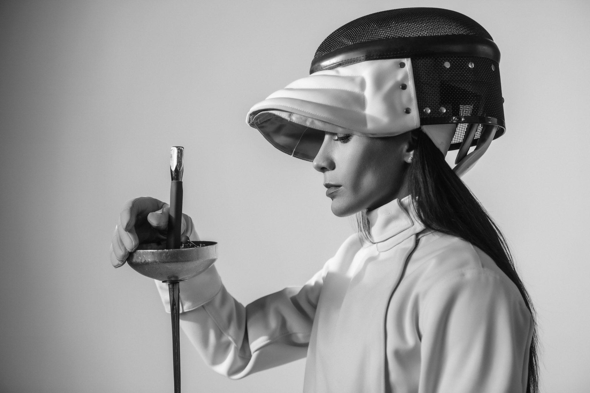 Рекламная съемка для Элина Исаева. Ph Постникова, md Элина Исаева. Девушка в белом фехтовальном костюме, с маской и саблей, на белом фоне, чб
