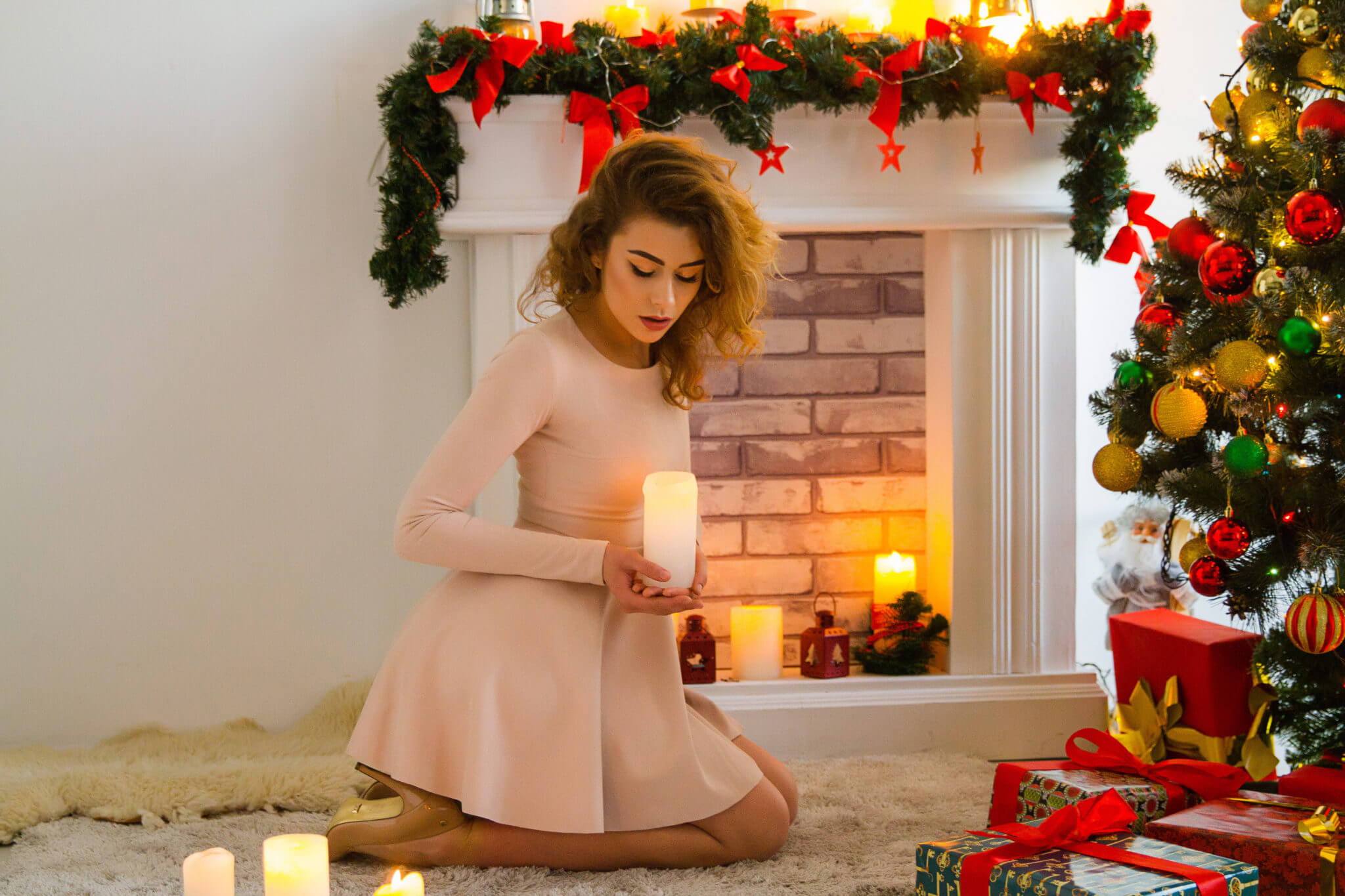 Новогодняя фотосессия, молодая девушка в платье на фоне камина и новогодней елки с зажженной свечой в руках