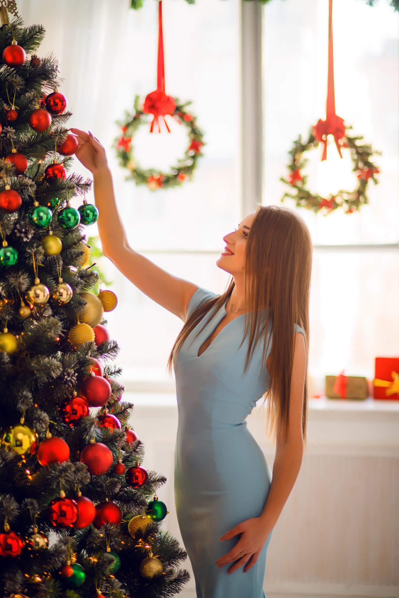 Новогодняя фотосессия, молодая девушка в платье на фоне окна с новогодними украшениями и новогодней елки