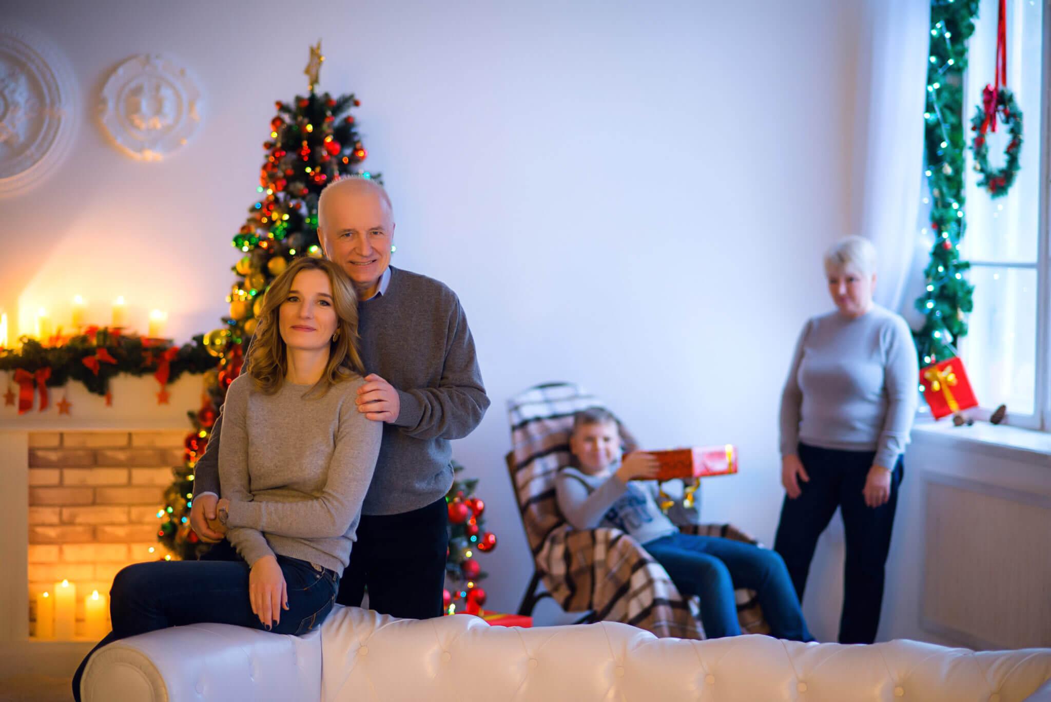 Новогодняя фотосессия, семья из четырех человек на фоне окна, новогодних украшений и елки