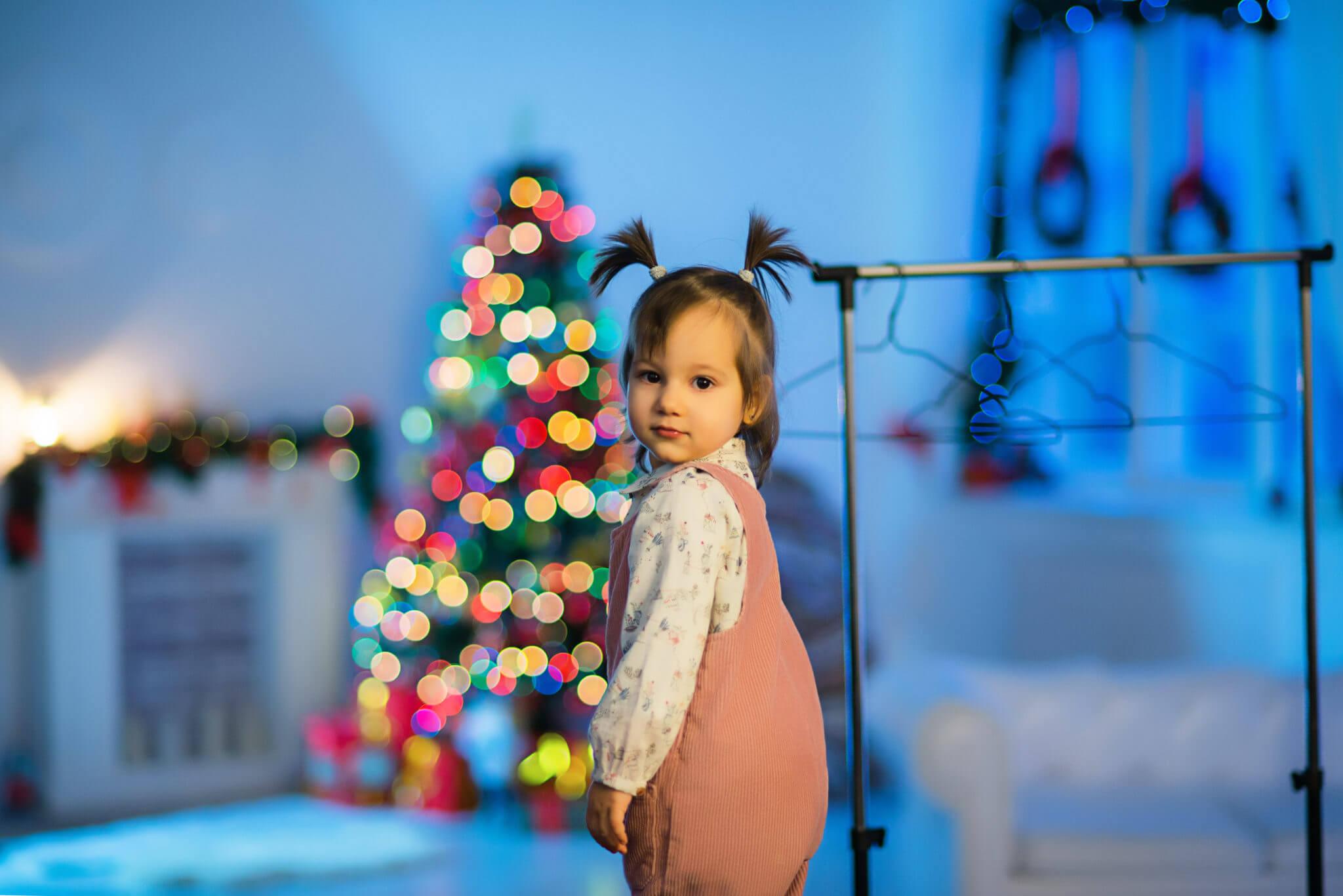 Новогодняя фотосессия, ребенок на фоне горящей новогодней елки