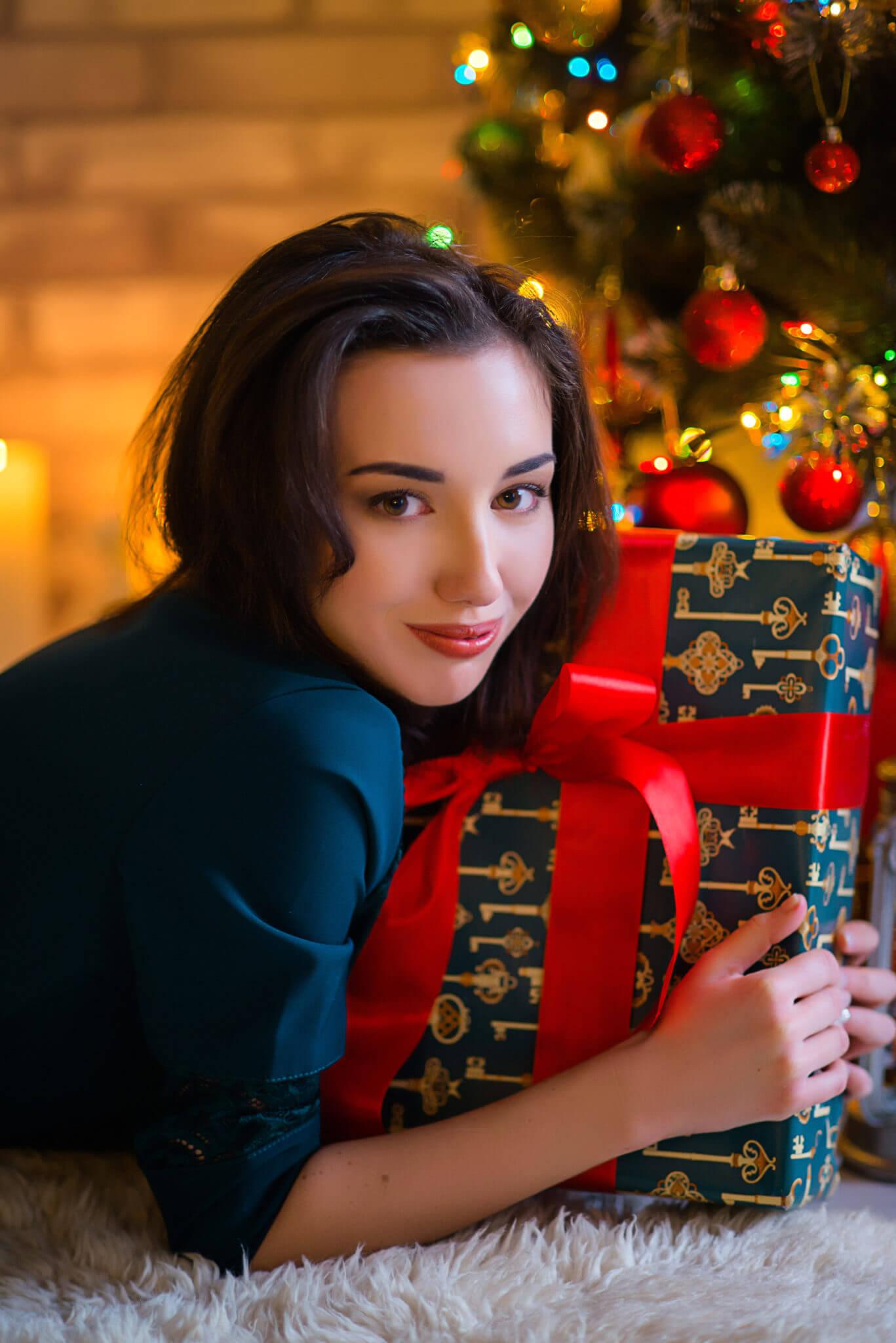 Новогодняя фотосессия, молодая девушка с подарком в руках под новогодней елкой