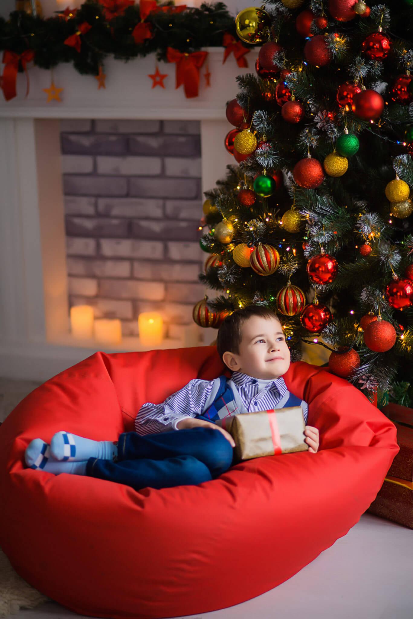 Новогодняя фотосессия, ребенок с подарком в руках лежит на красной подушке под новогодней елкой