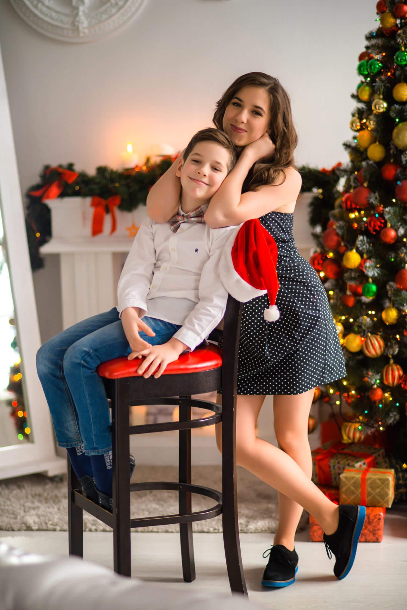 Новогодняя фотосессия, мать и сын, ребенок сидит на высоком стуле, на фоне новогодней елки