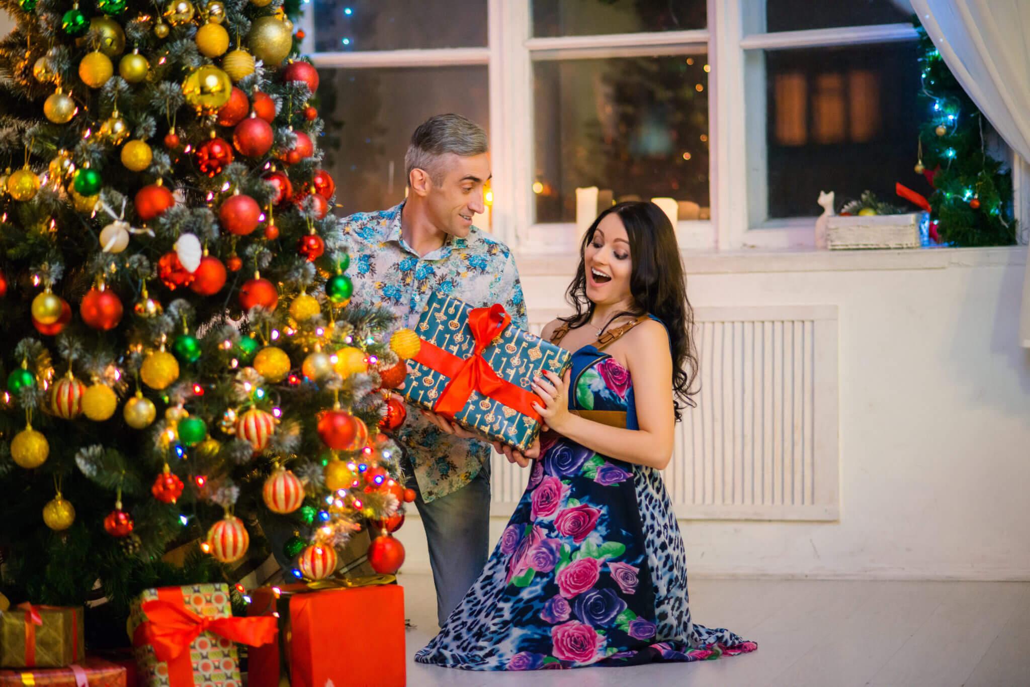 Новогодняя фотосессия, семейная пара на фоне окна и новогодней елки