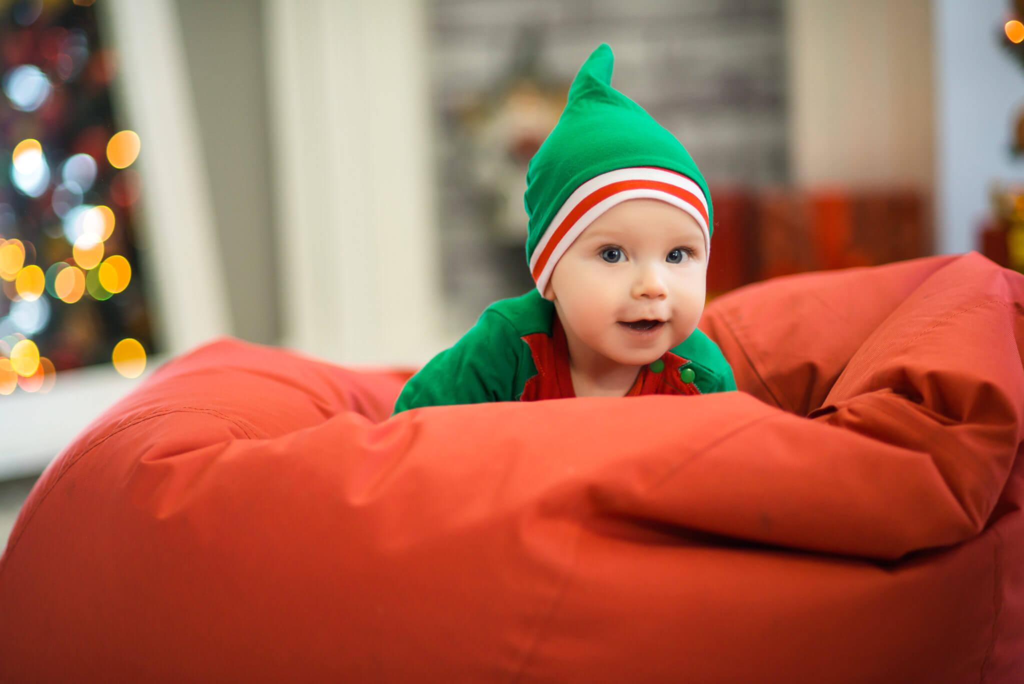Новогодняя фотосессия, ребенок в костюме эльфа на красной подушке