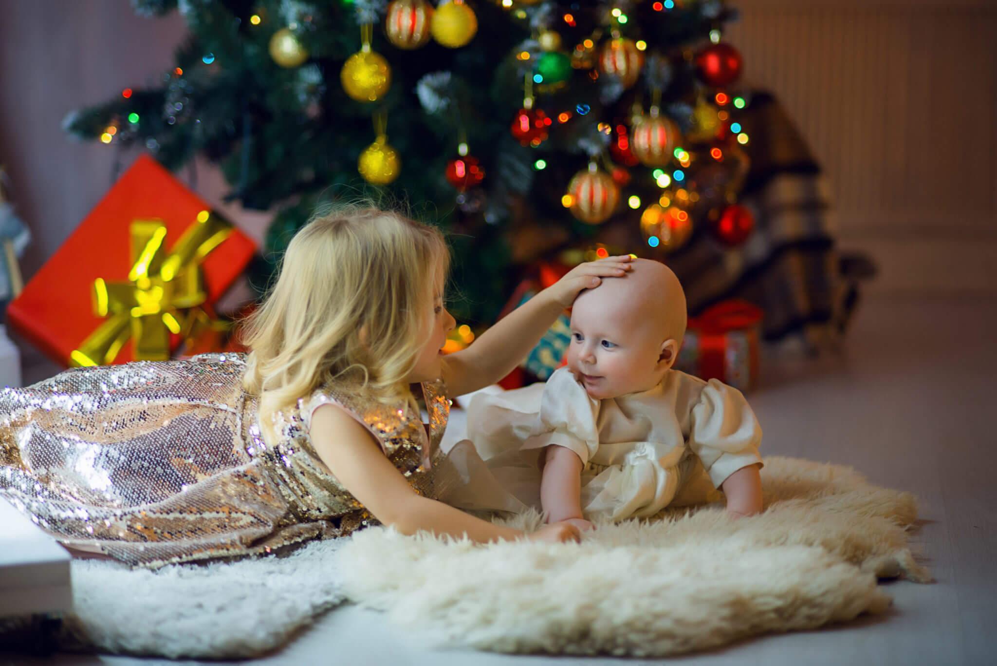 Новогодняя фотосессия, 2 ребенка на ковре на фоне новогодней елки