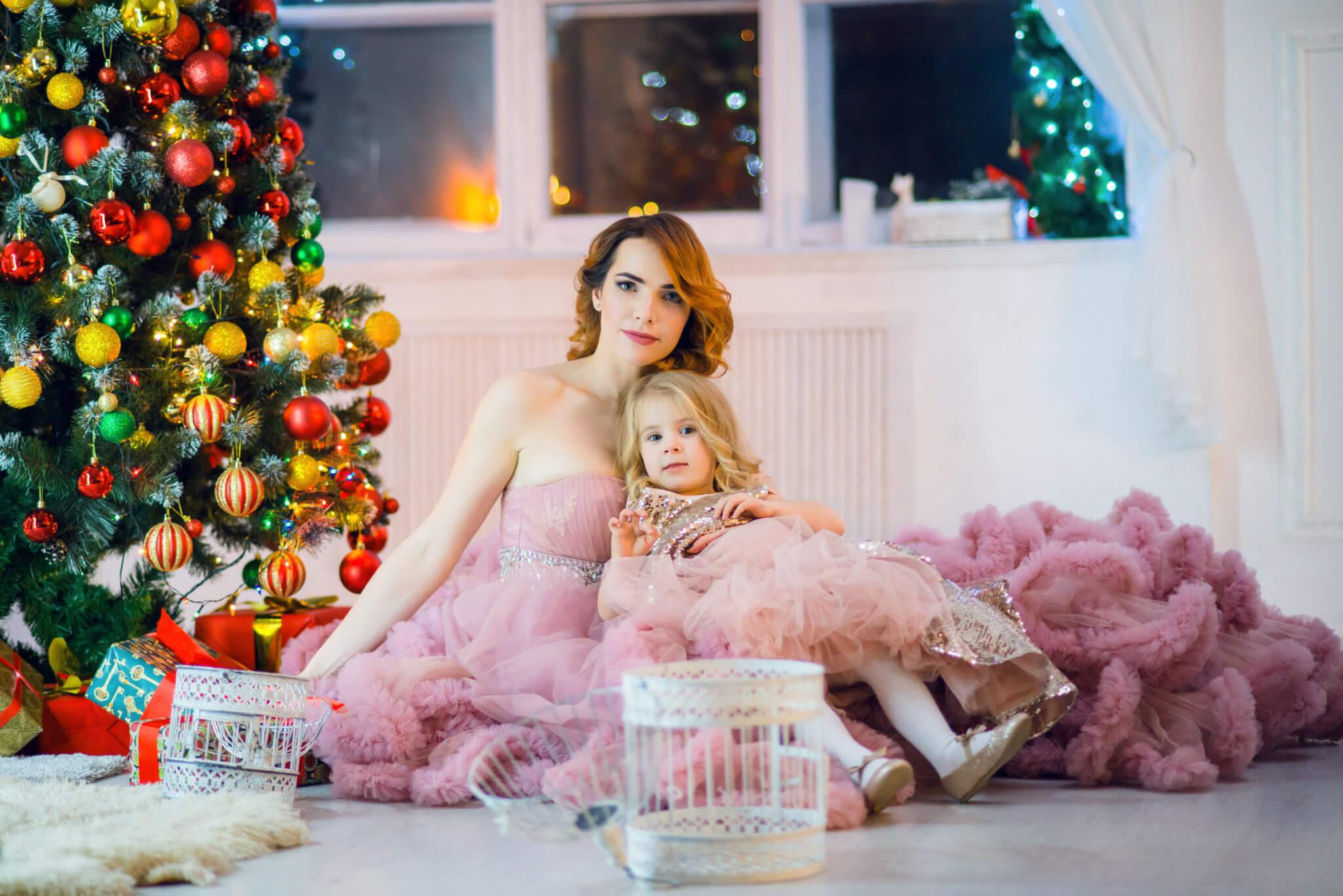 Новогодняя фотосессия, мать и дочь в пышных розовых платьях на фоне новогодней елки