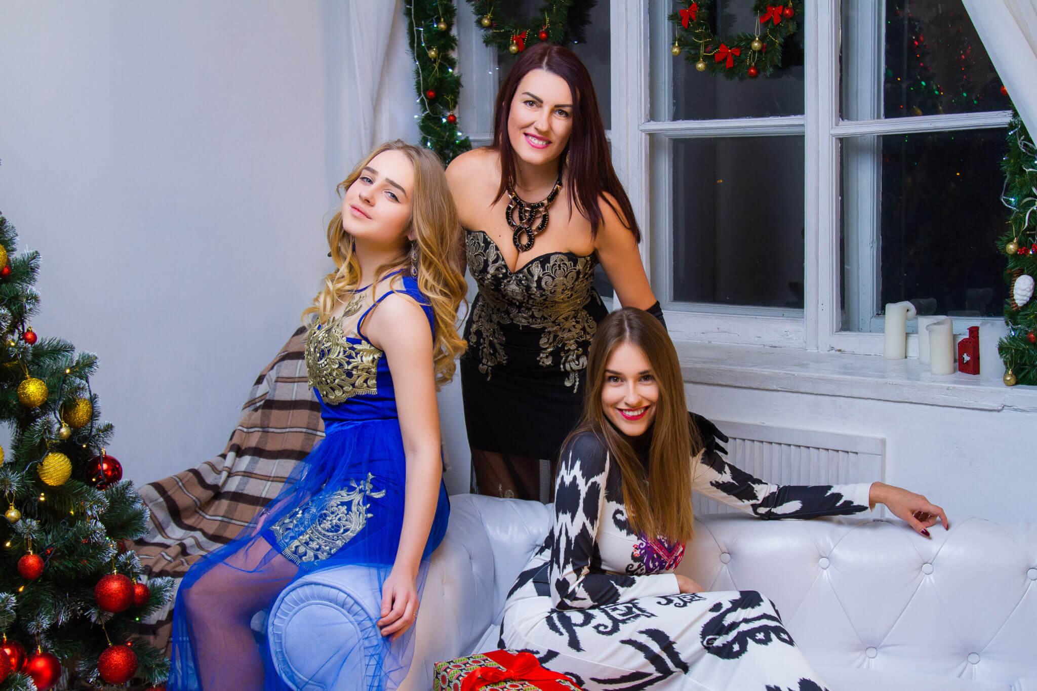 Новогодняя фотосессия, 3 девушки сидят на белом диване на фоне елки у камина