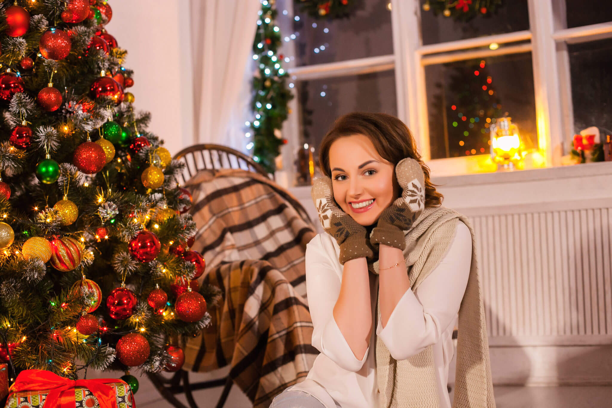 Новогодняя фотосессия, девушка на фоне новогодней елки и кресла-качалки