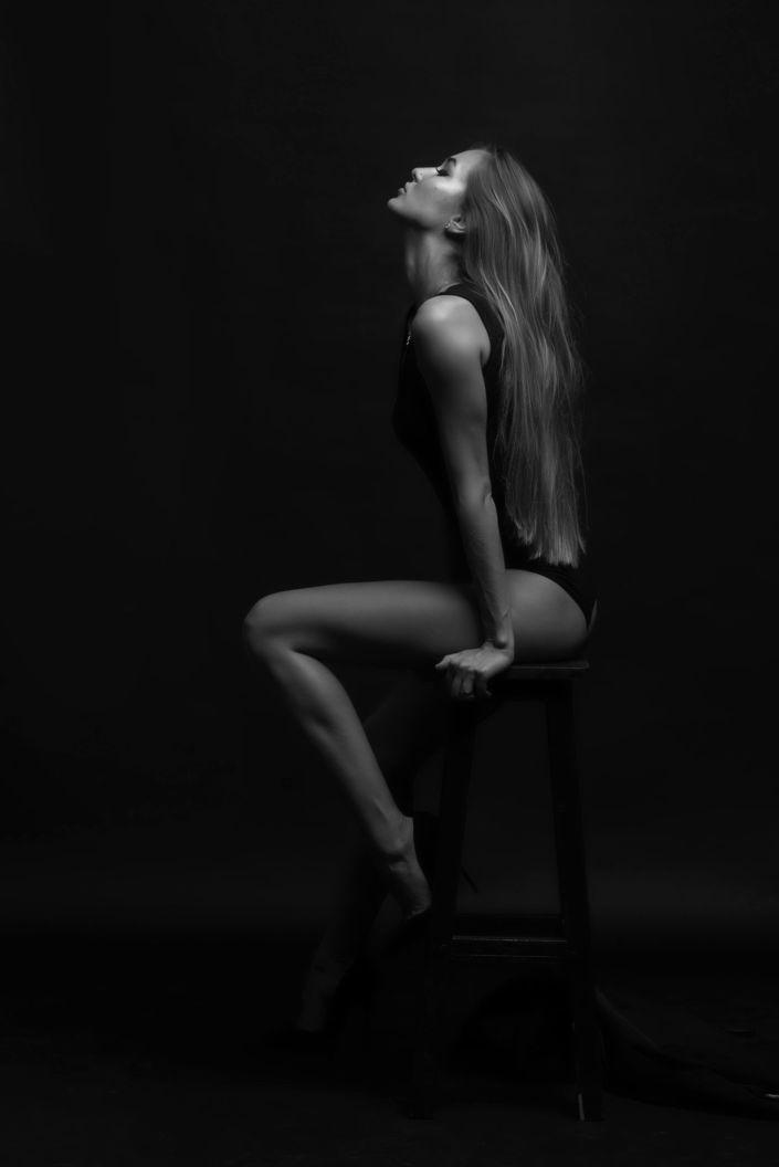 Модельные тесты, чб фото, девушка в купальнике на стуле на черном фоне