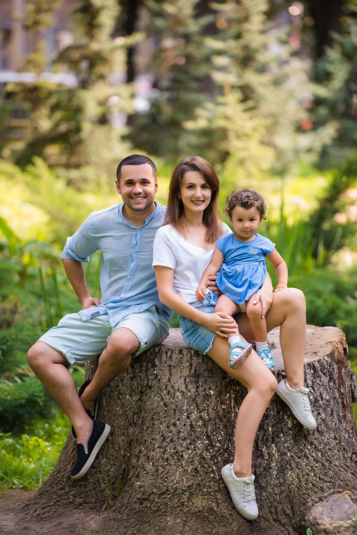 Семейная фотосессия на природе, семья из трех человек сидят на пеньке