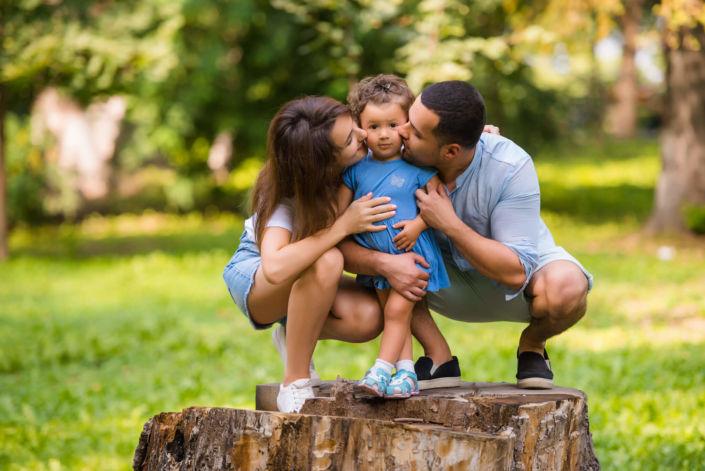 Семейная фотосессия, на природе, семья из трех человек стоят на пеньке