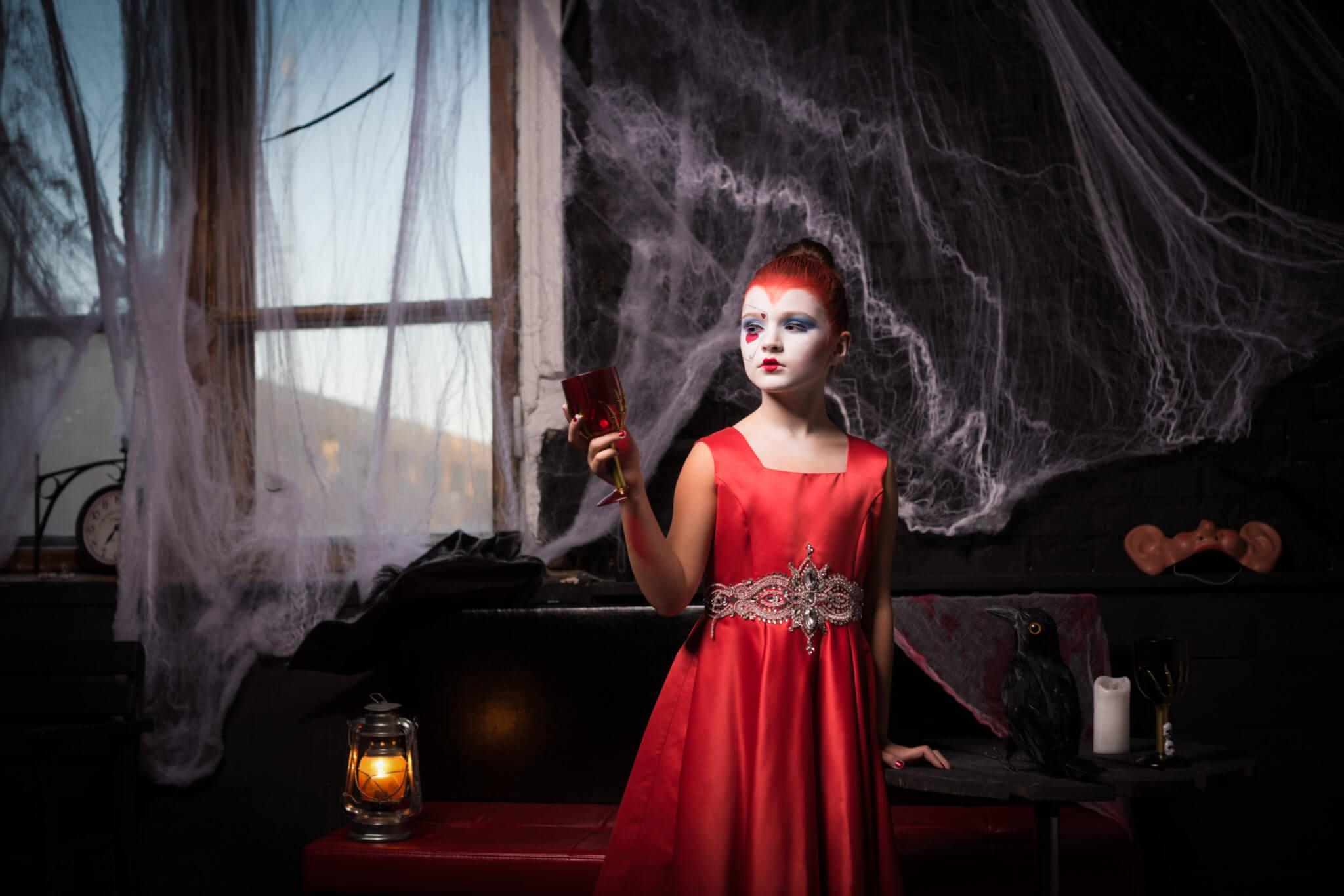 Фотосессия на Хэллоуин, ph Постникова Алиса, девочка в красном платье с бокалом в руке на фоне черной стены и паутины