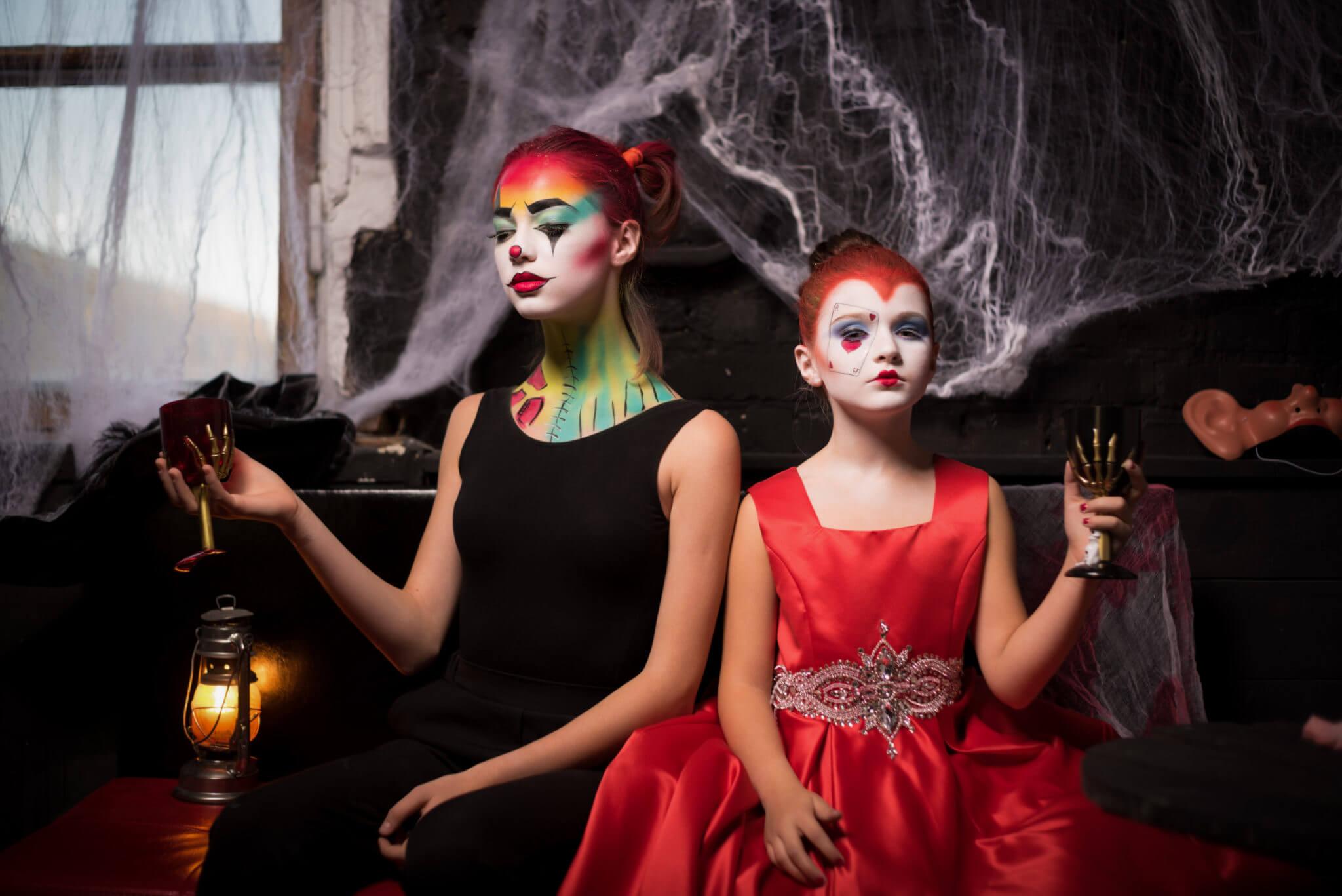 Фотосессия на Хэллоуин, ph Постникова Алиса, 2 девочки с фейс-артом и бокалом в руках на фоне черной стены в паутине