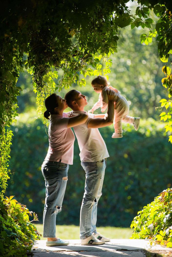 Семейная фотосессия, на природе, семья из трех человек в тени винограда