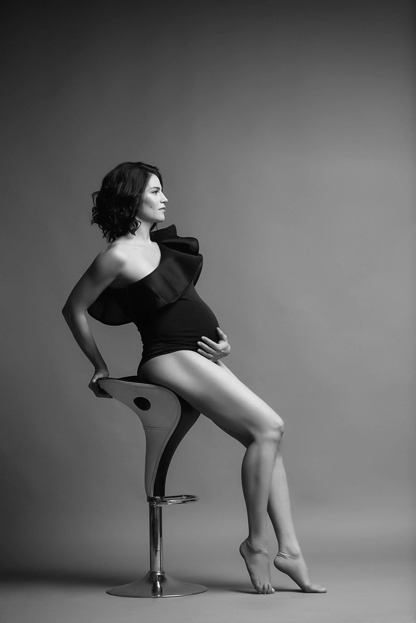 Портфолио фотосессии беременности в студии, девушка белом фоне на стуле, чб фотография