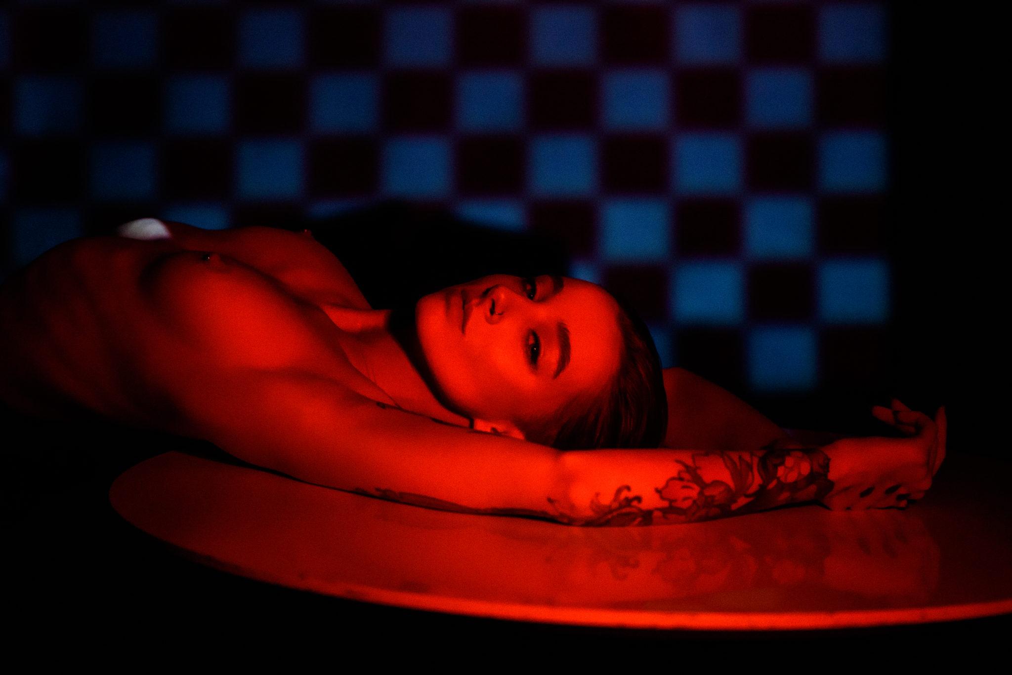 Портфолио ню фотосессии, фотограф Алиса Постниковой, модель Валерия Ионеску, обнаженная на белом столе спиной, красный свет, цветное фото