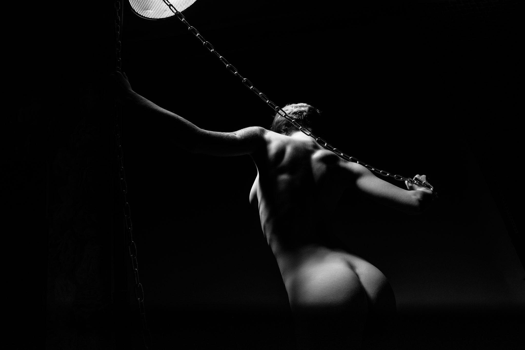 Портфолио ню фотосессии, фотограф Алиса Постниковой, модель Валерия Ионеску, обнаженная с цепями в руках под прожектором, чб фото