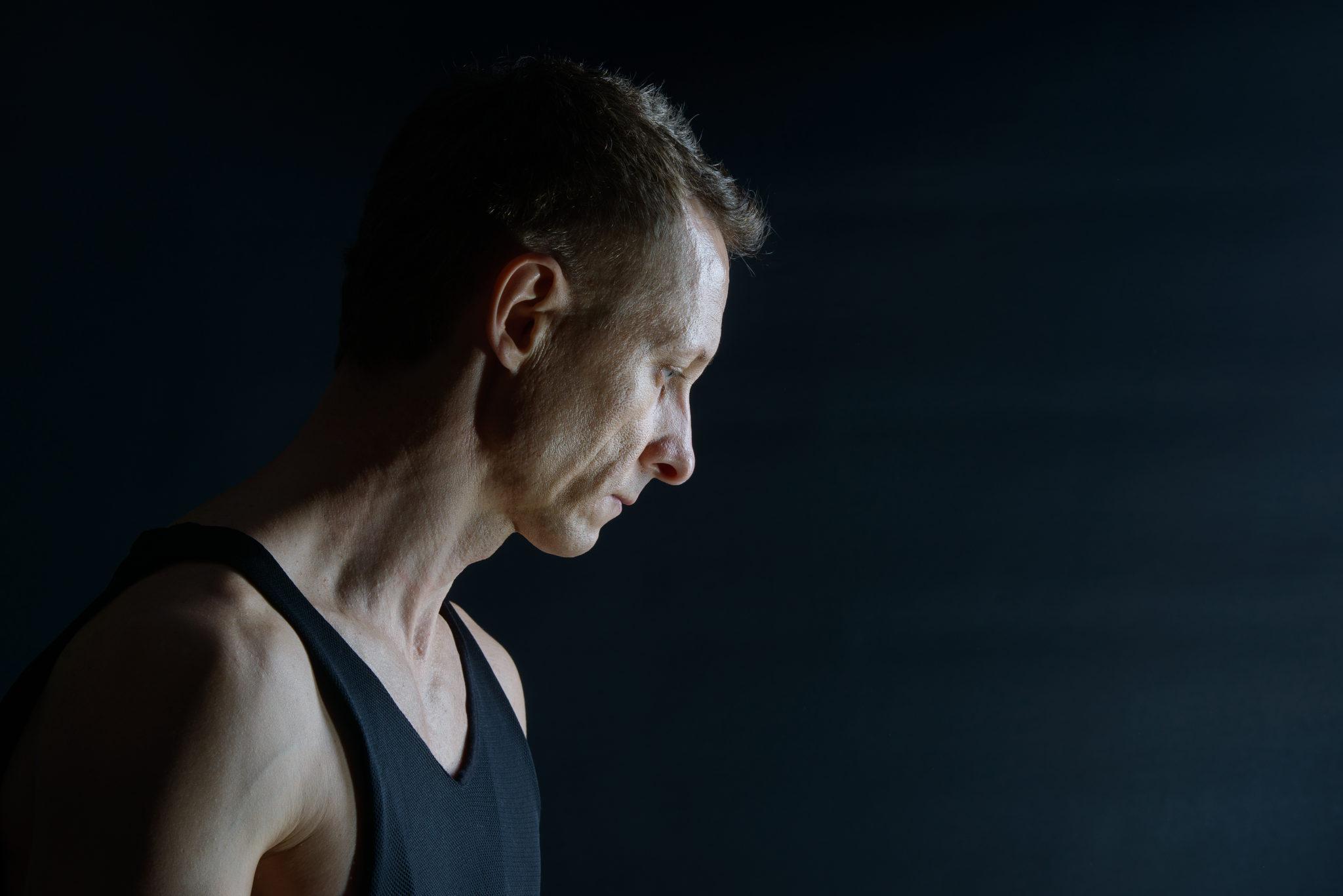 Мужская фотосессия в студии, ph Постникова, цветное фото, мужской портрет в профиль на черном фоне
