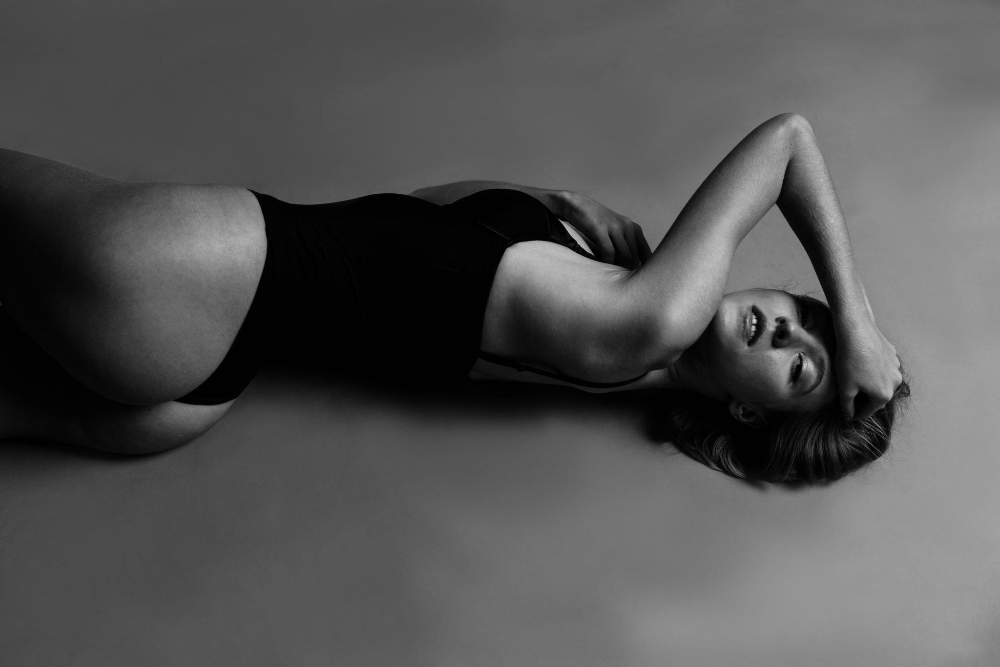 Модельные тесты, чб фото, девушка в черном купальнике лежит на белом фоне