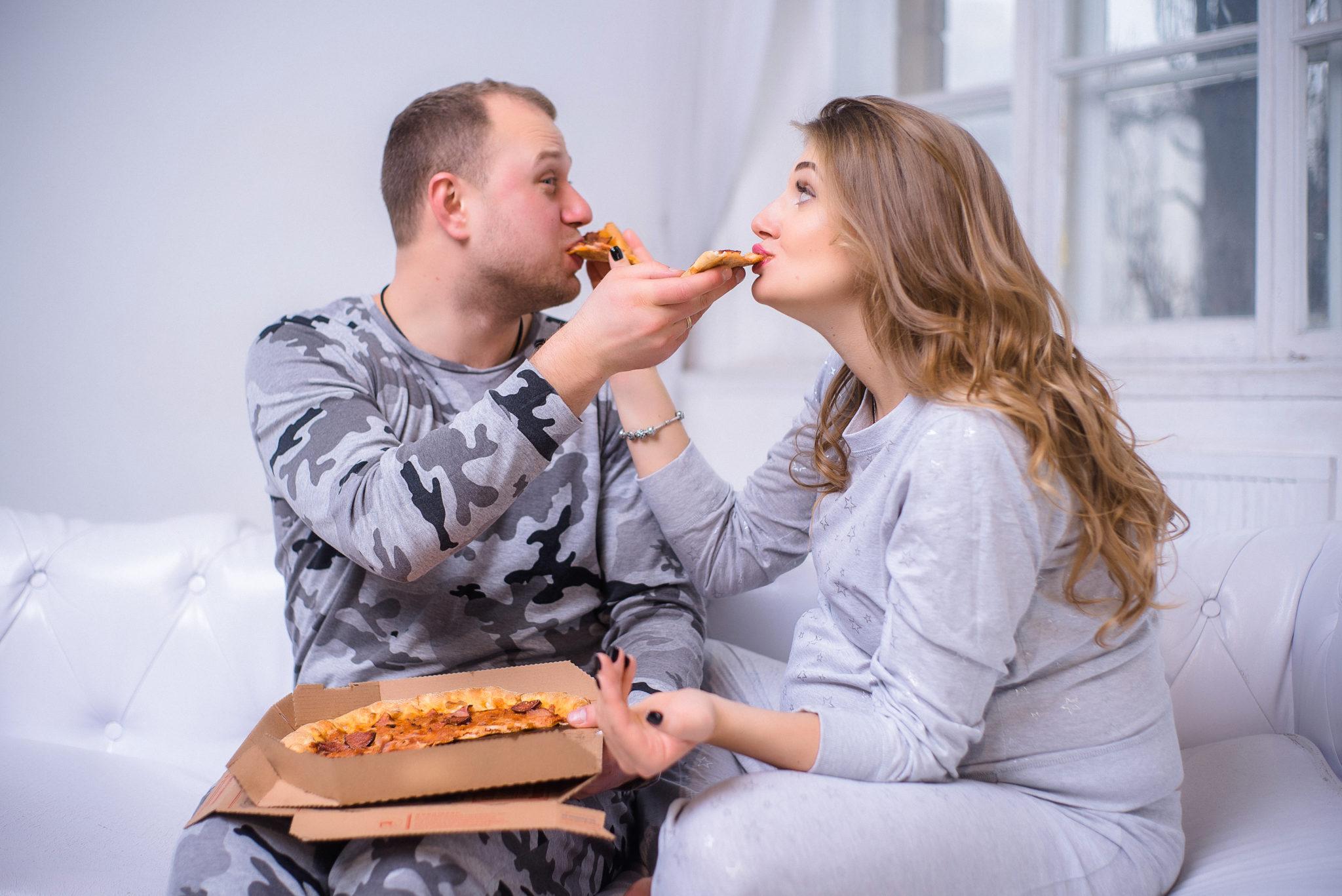 Портфолио фотосессии беременности в студии, фотограф Алиса Постникова, фотография пары, пара кормит друг друга пиццей