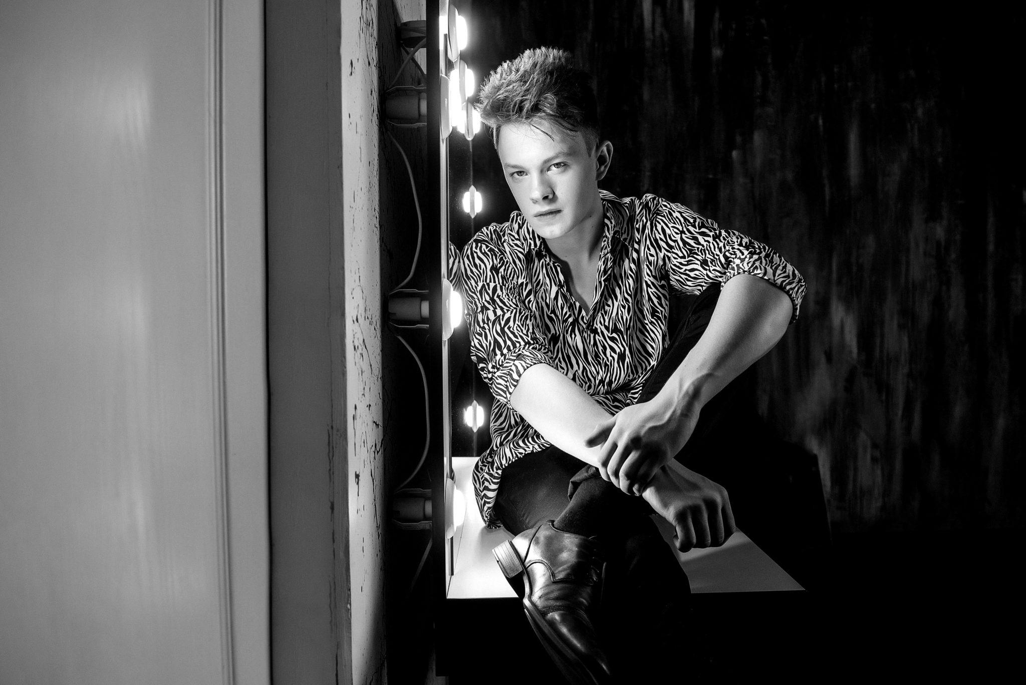 Мужская фотосессия в студии, ph Постникова, парень в рубашке сидит на визажном столе, чб фотография