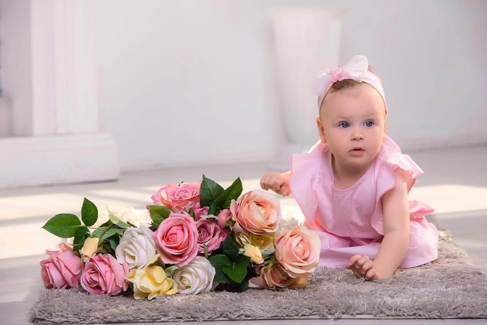 Детская фотосессия, ребенок на ковре рядом с цветами