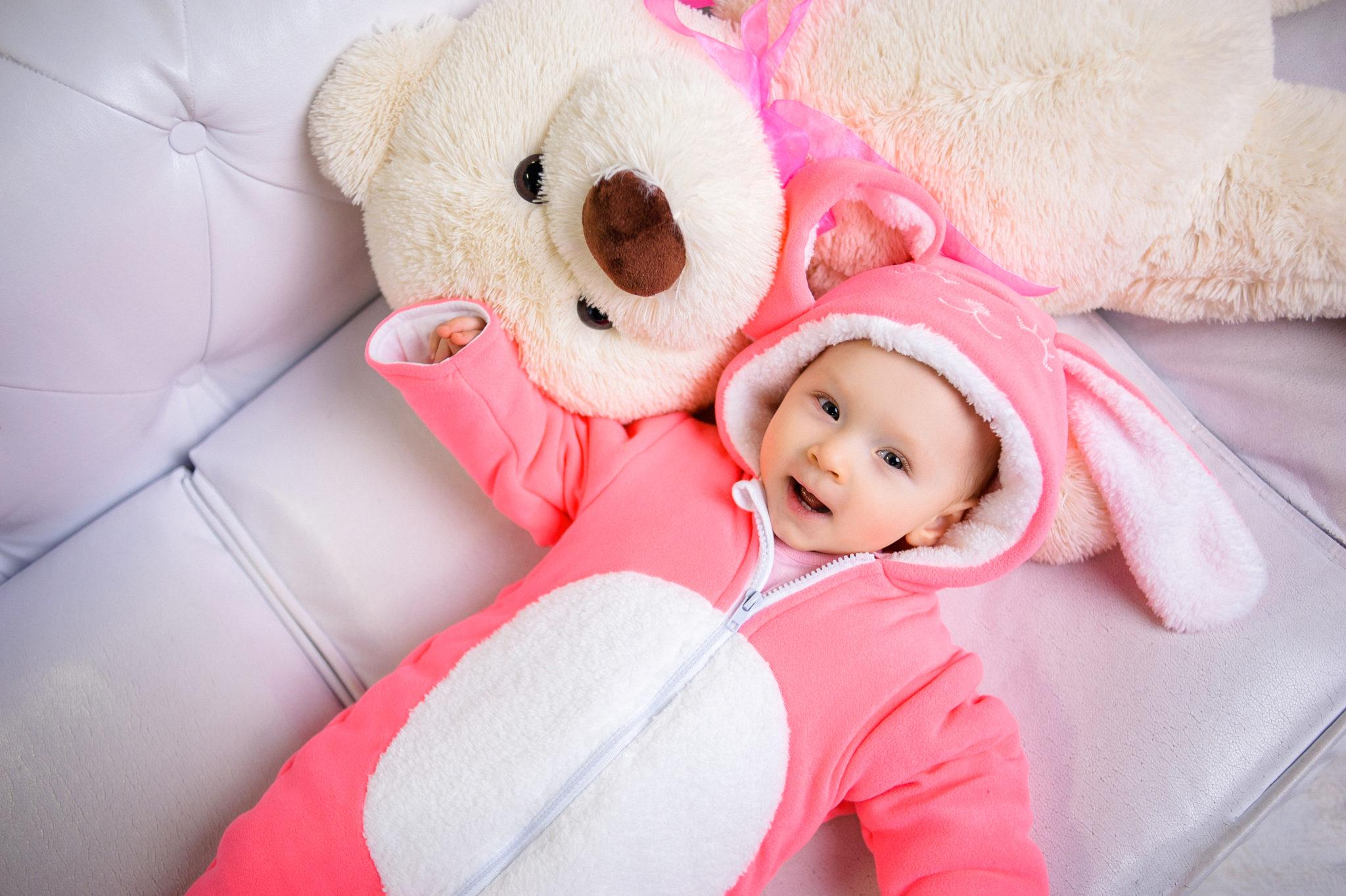 Детская фотосессия, ребенок лежит на белом диване с белым медведем