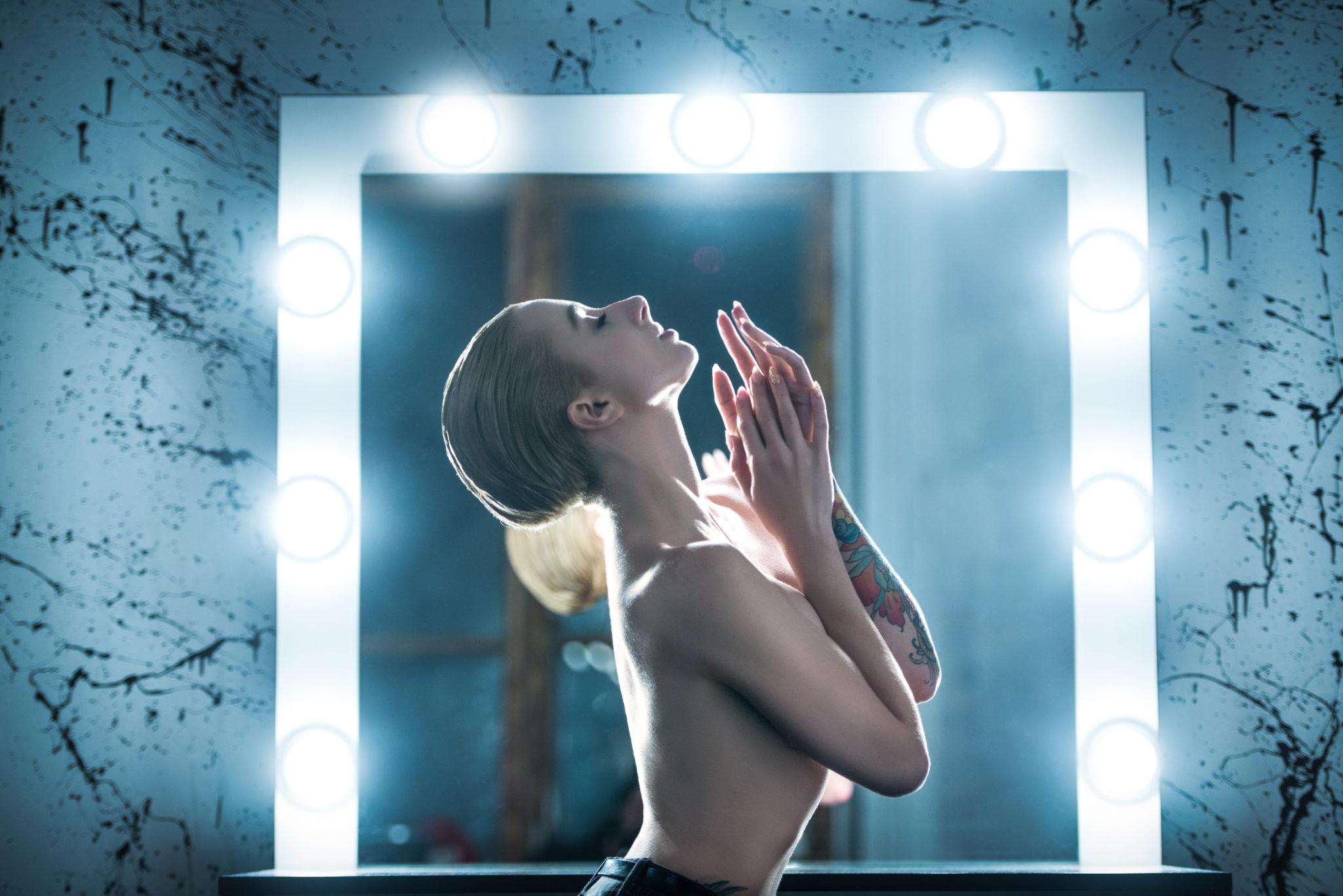 Экспресс фотосессия, девушка топлес в пол-оборота к фотографу, на фоне визажного стола