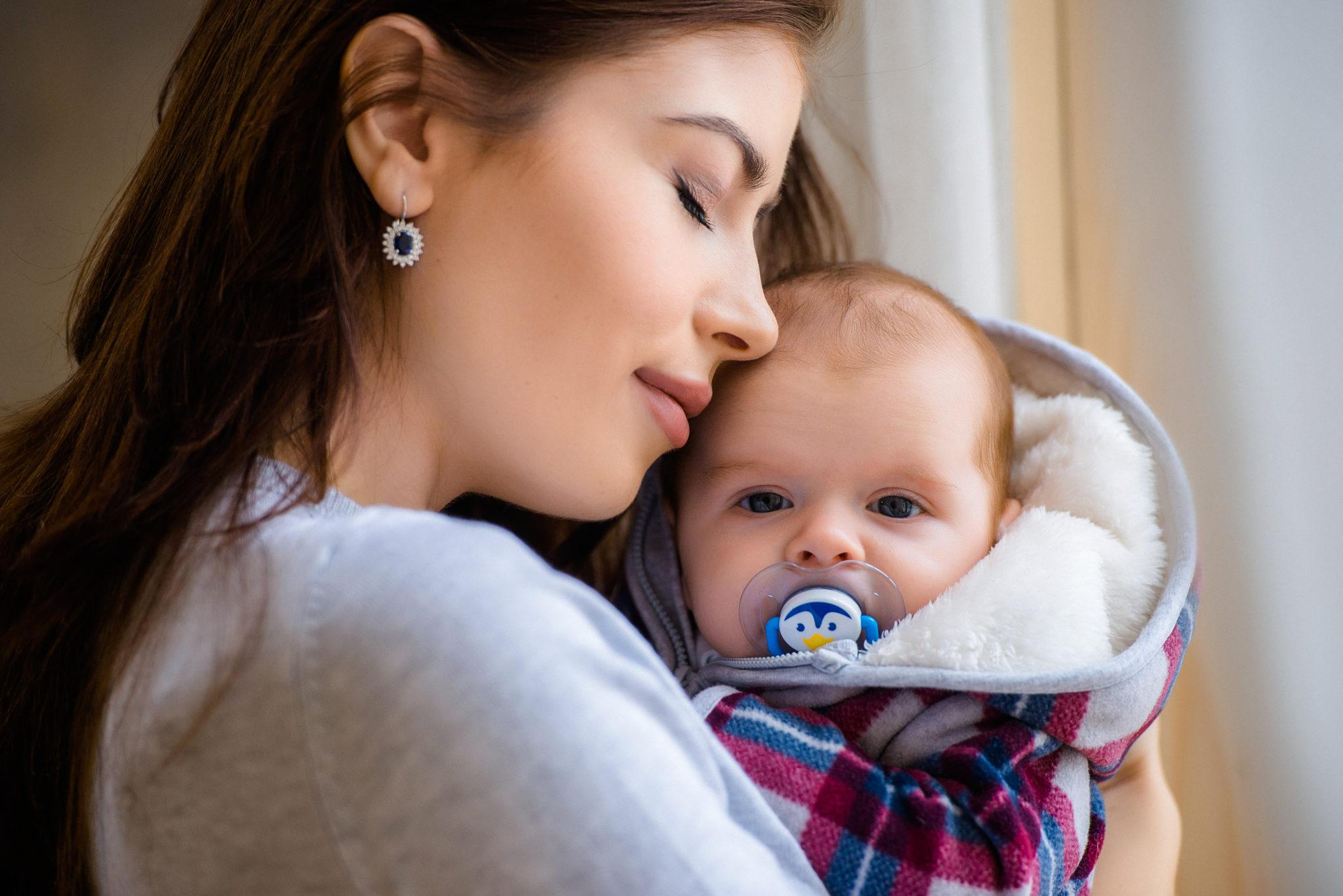 Портфолио студийная семейная фотосессия, мать обнимает ребенка рядом с окном