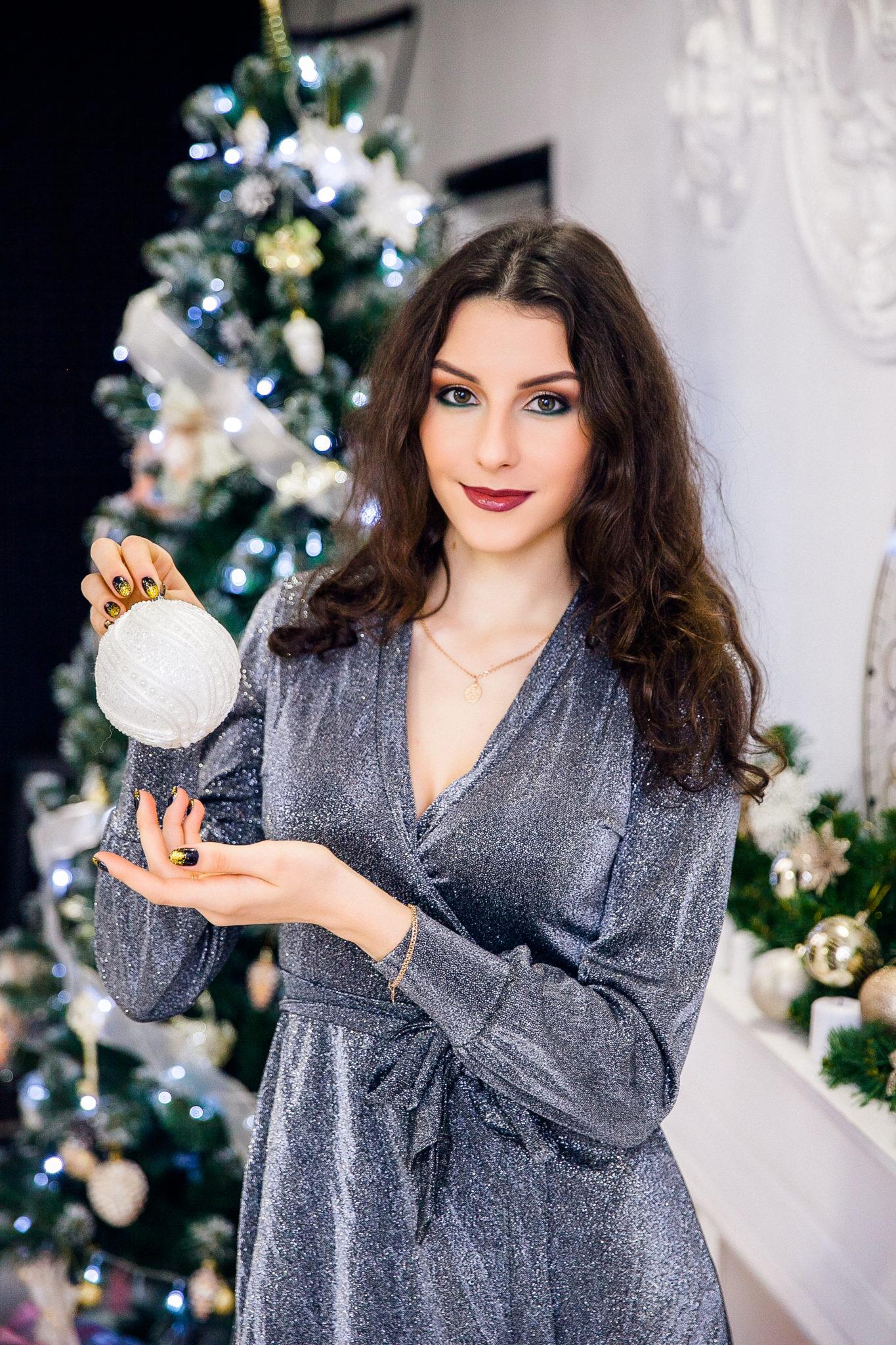 Новогодняя фотосессия, девушка в серебристом платье с елочным украшением в руках на фоне елки