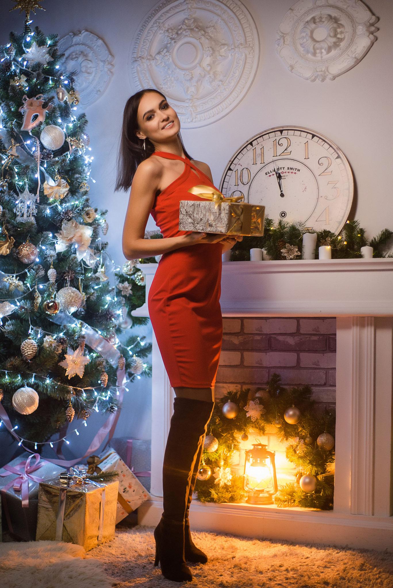 Новогодняя фотосессия, девушка в красном платье с подарком в руках на фоне елки