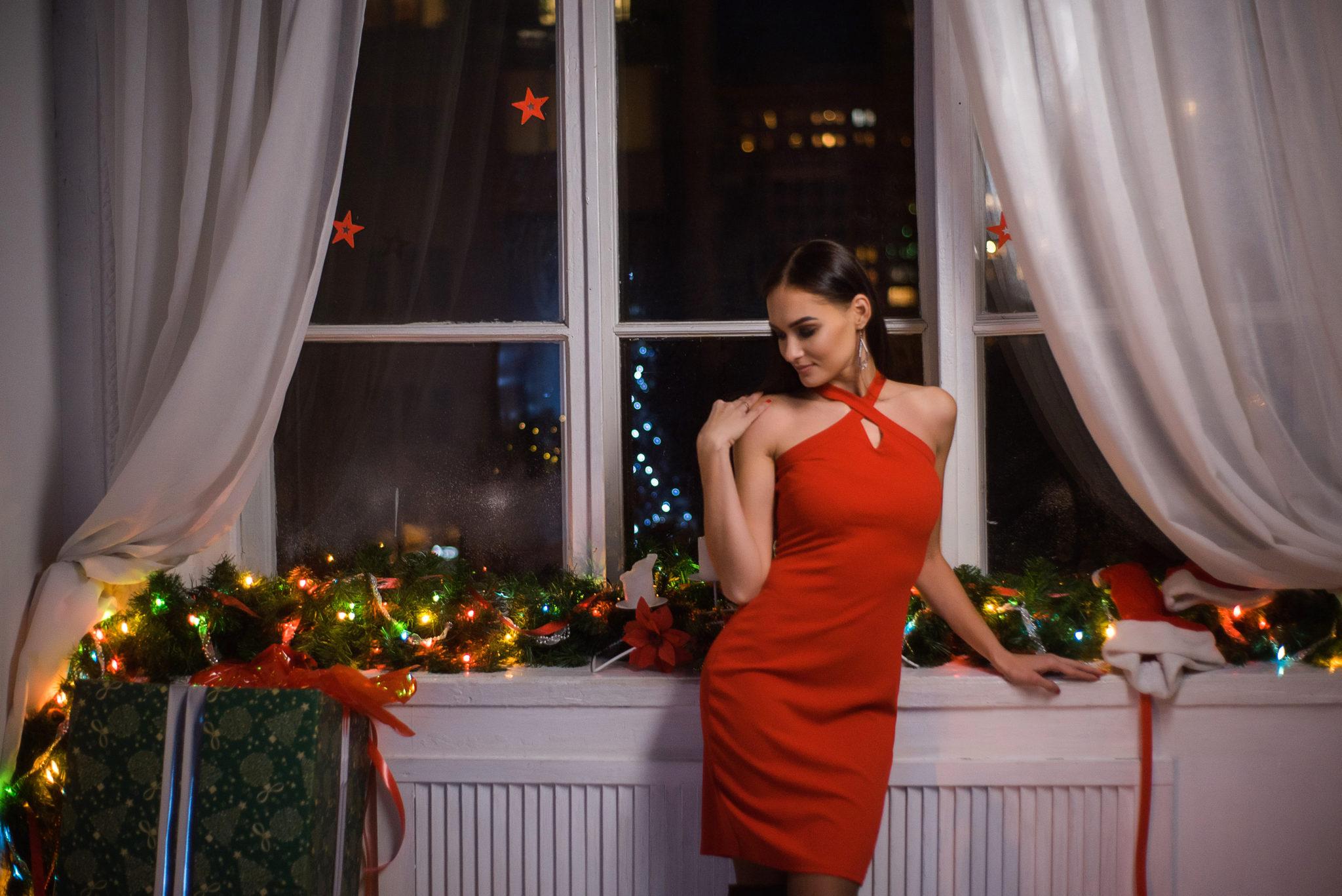 Новогодняя фотосессия, девушка в красном платье на фоне украшенного в новогоднем стиле окна