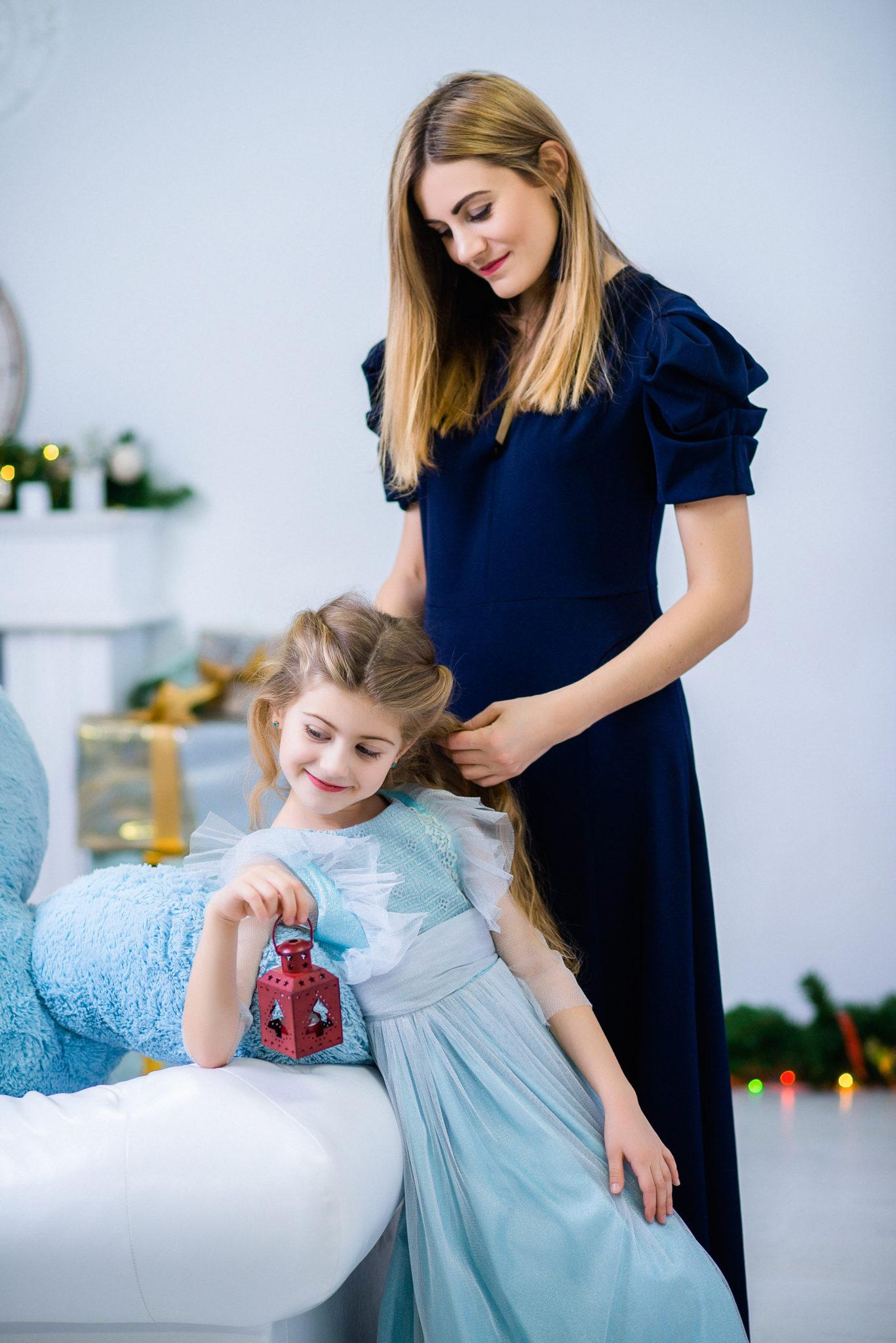 Новогодняя семейная фотосессия, мама с дочерью рядом с белым диваном и на фоне новогодних украшений