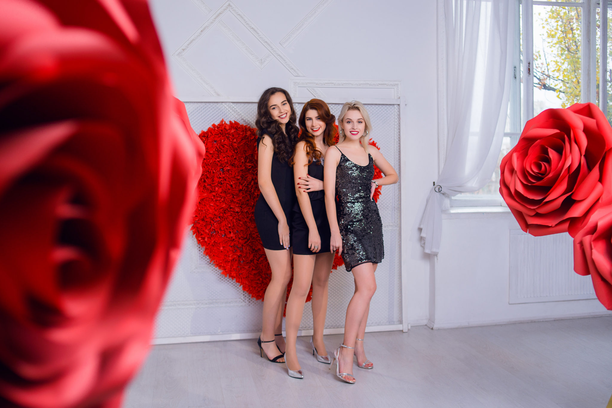 Девичник в студии, 3 девушки в платьях на фоне бумажного сердца и цветов